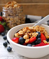 white bowl with yogurt topped with granola and fresh fruit
