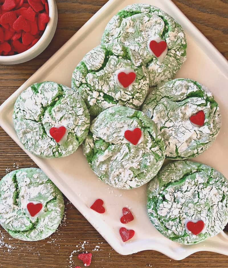 Overhead view of white plate with bright green cookies and single heart candy