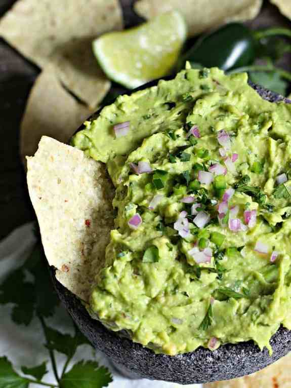Easy Homemade Guacamole recipe: fresh bright flavor comes together in about 5 minutes plus tips on how to select a ripe avocado and safely remove the pit.