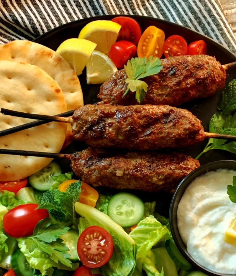 closeup of 3 grilled koftas on wood skewers surrounded by side salad