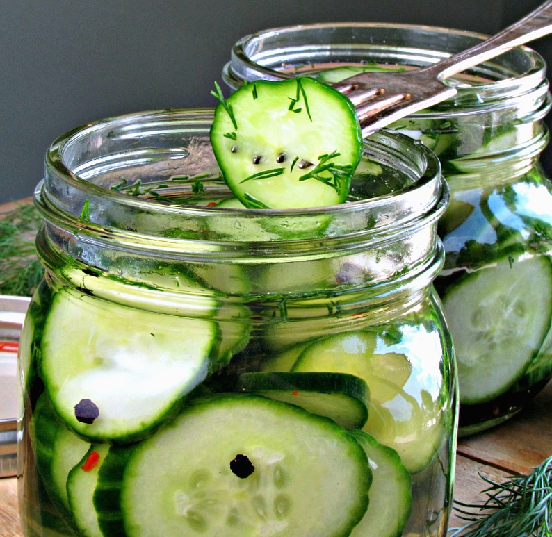 side view of pickles in jar and fork spearing a single pickle