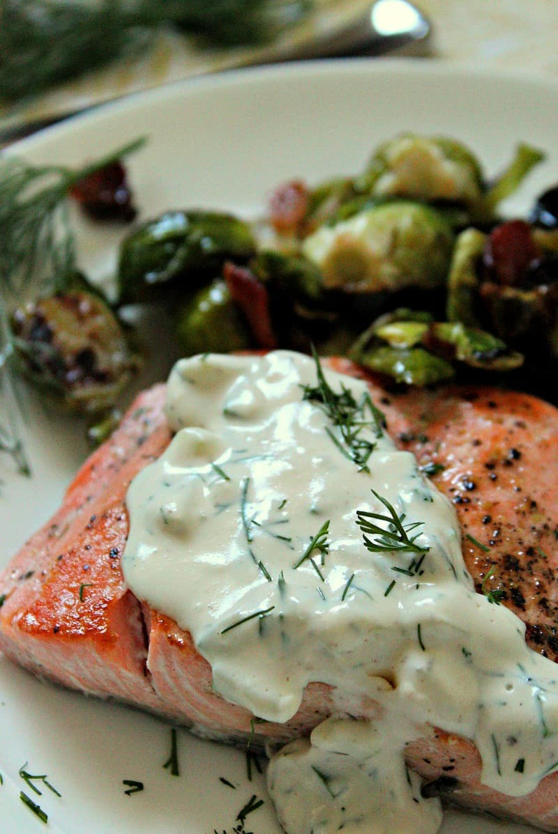 salmon filet topped with creamy cucumber dill sauce served with brussels sprouts