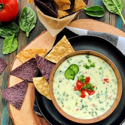 bowl of spinach queso garnished with diced tomatoes and jalapeno