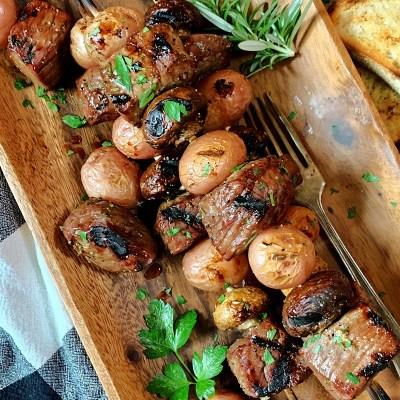 steak, mushroom, potato kabobs garnished with rosemary sprigs