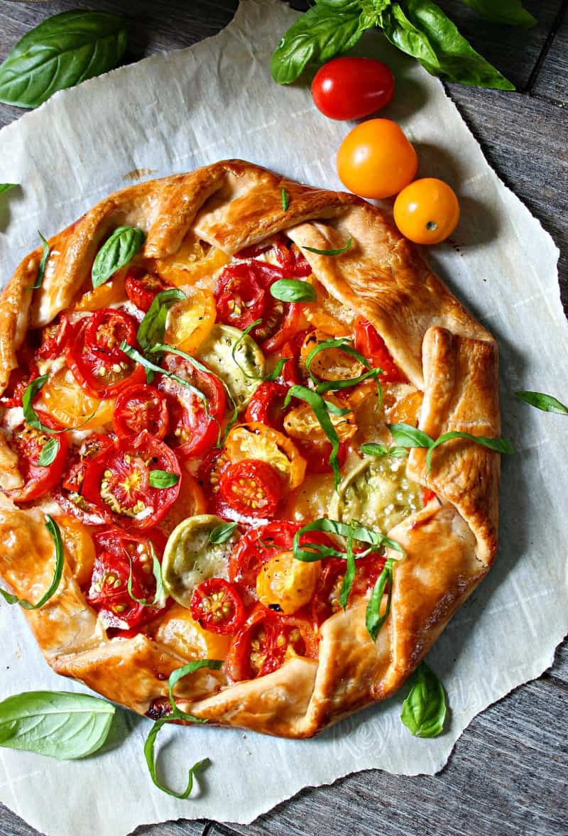 overhead view of whole tomato galette garnished with sliced basil