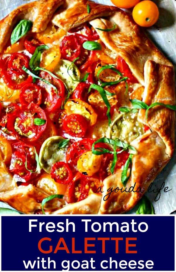 pin for pinterest showing tomato galette on white parchment paper