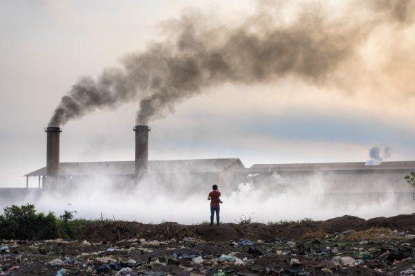 Un bambino al cospetto di un ambiente inquinato da fumi e rifiuti