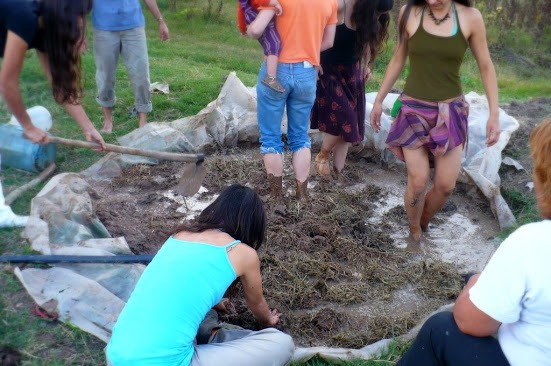 Grupo de participantes de la huerta Santa Elena preparando adobe