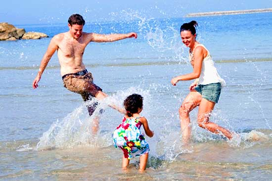 Father, mother, and little daughter playing on beach and having holiday fun