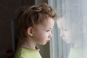 child stares out window looking sad or worried