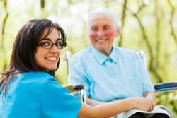 caregiver smiling with an elderly woman in a wheelchair