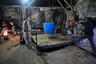 A Palestinian tunnel worker works on a machine for pulling containers filled by sand from inside a tunnel was collapsed partly due to the Egyptian army acts in Rafah, near the border between Egypt and the southern Gaza Strip. Egyptian Army sources said that about 805 tunnels connecting Egypt and Gaza have been demolished.