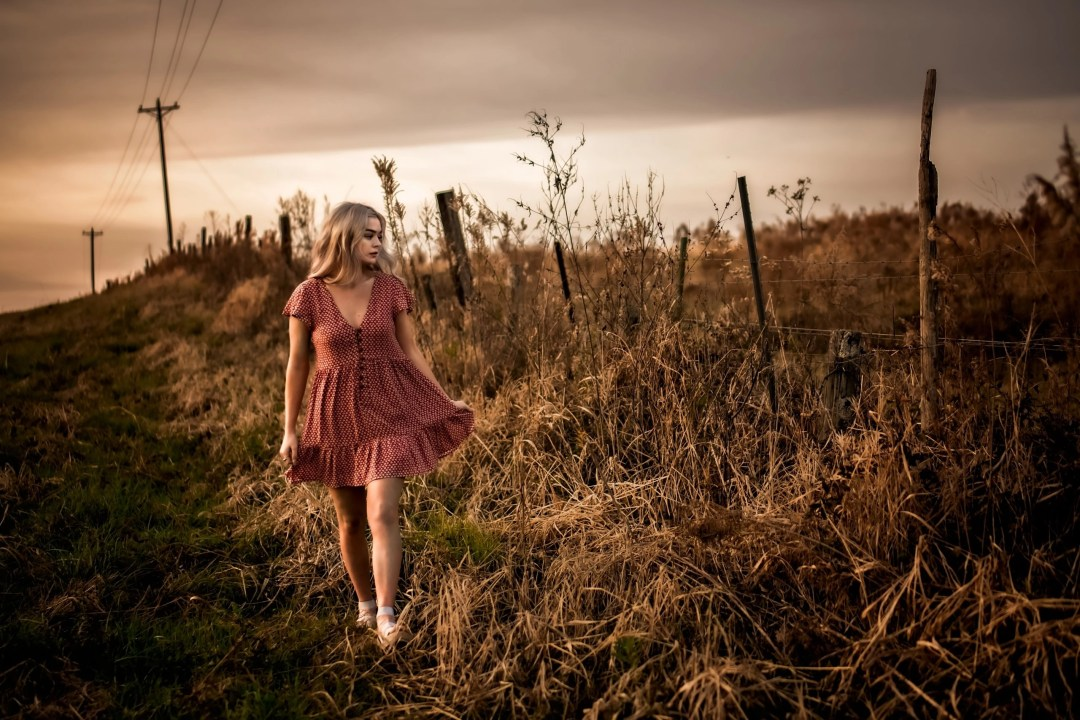 blonde senior in red dress walking along rustic field vintage creative photography