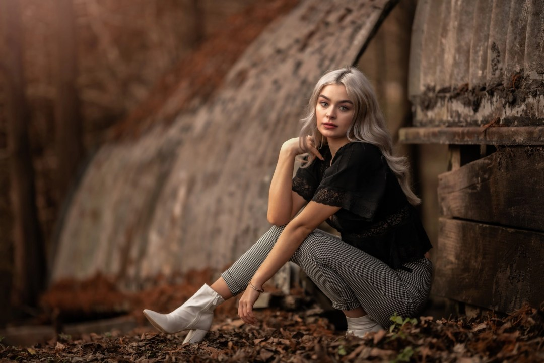 beautiful blonde senior photograph in black shirt checkered pants and white boots