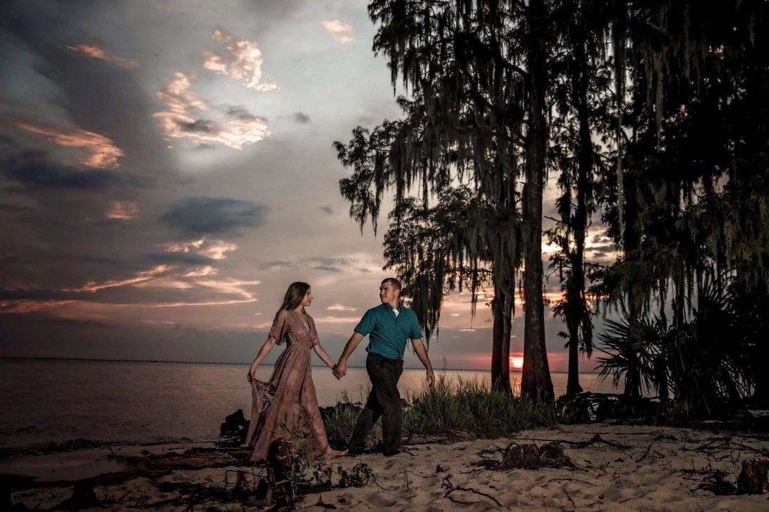 engaged couple holding hands at sunset on beach among trees and spanish moss