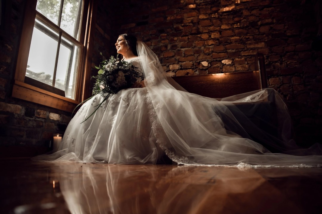 bridal wedding portrait sitting and gazing out of window smiling