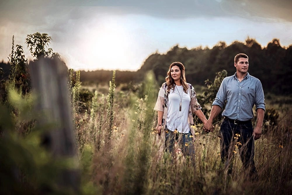 engagement photo outdoor holding hands in field