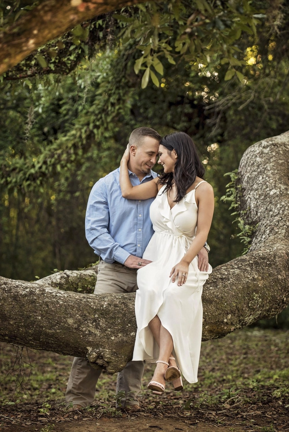 woman sitting on tree limp touching forehead to future husband