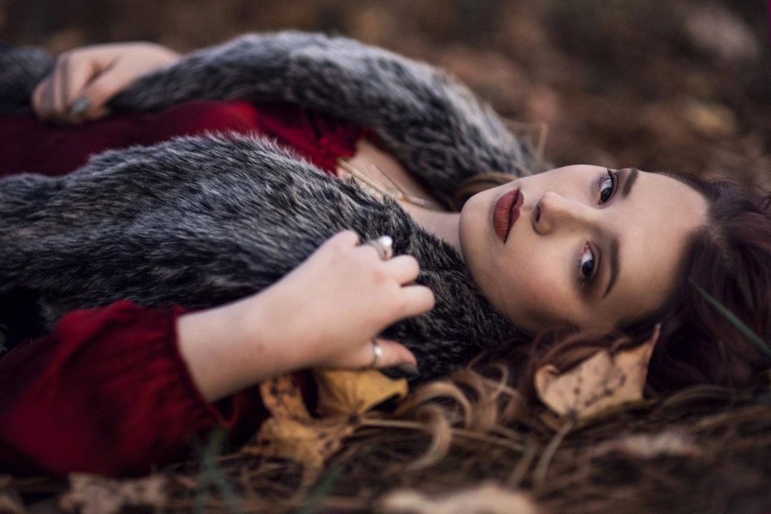 brunette senior photography portrait session laying in grass