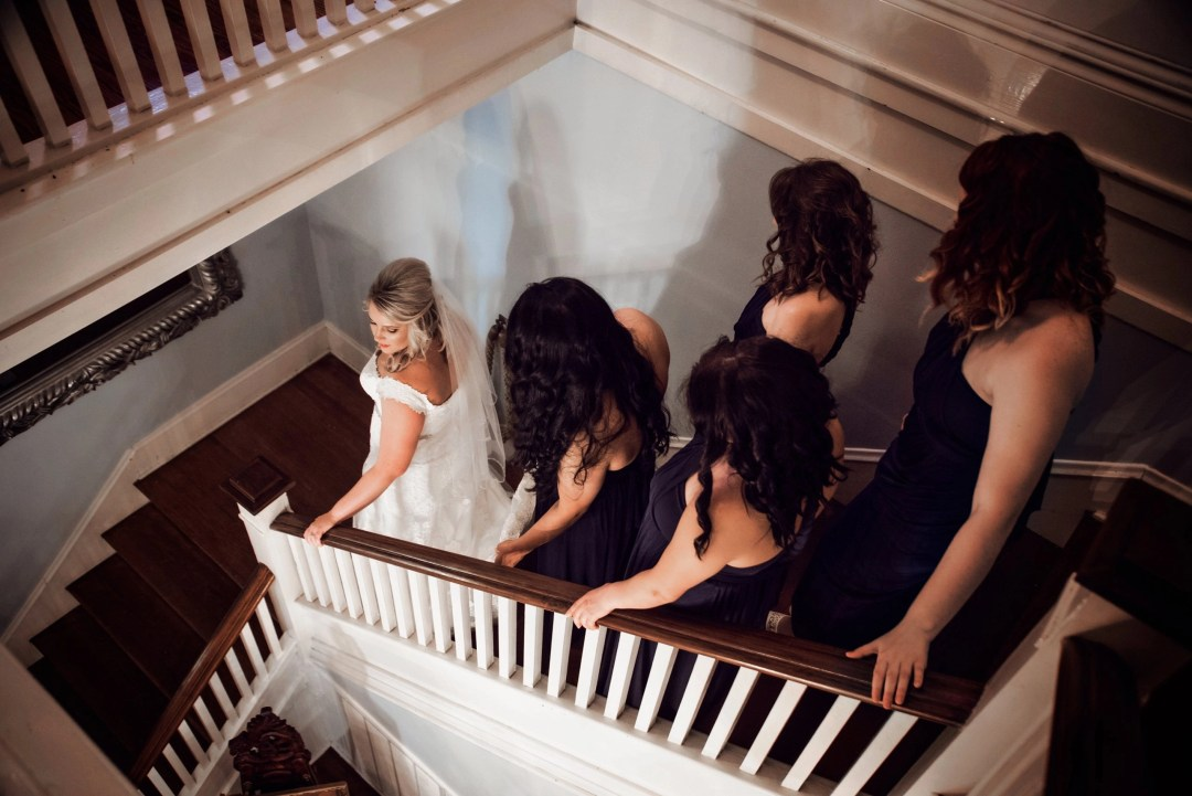 bride and bridesmaids descending down stairs on wedding day