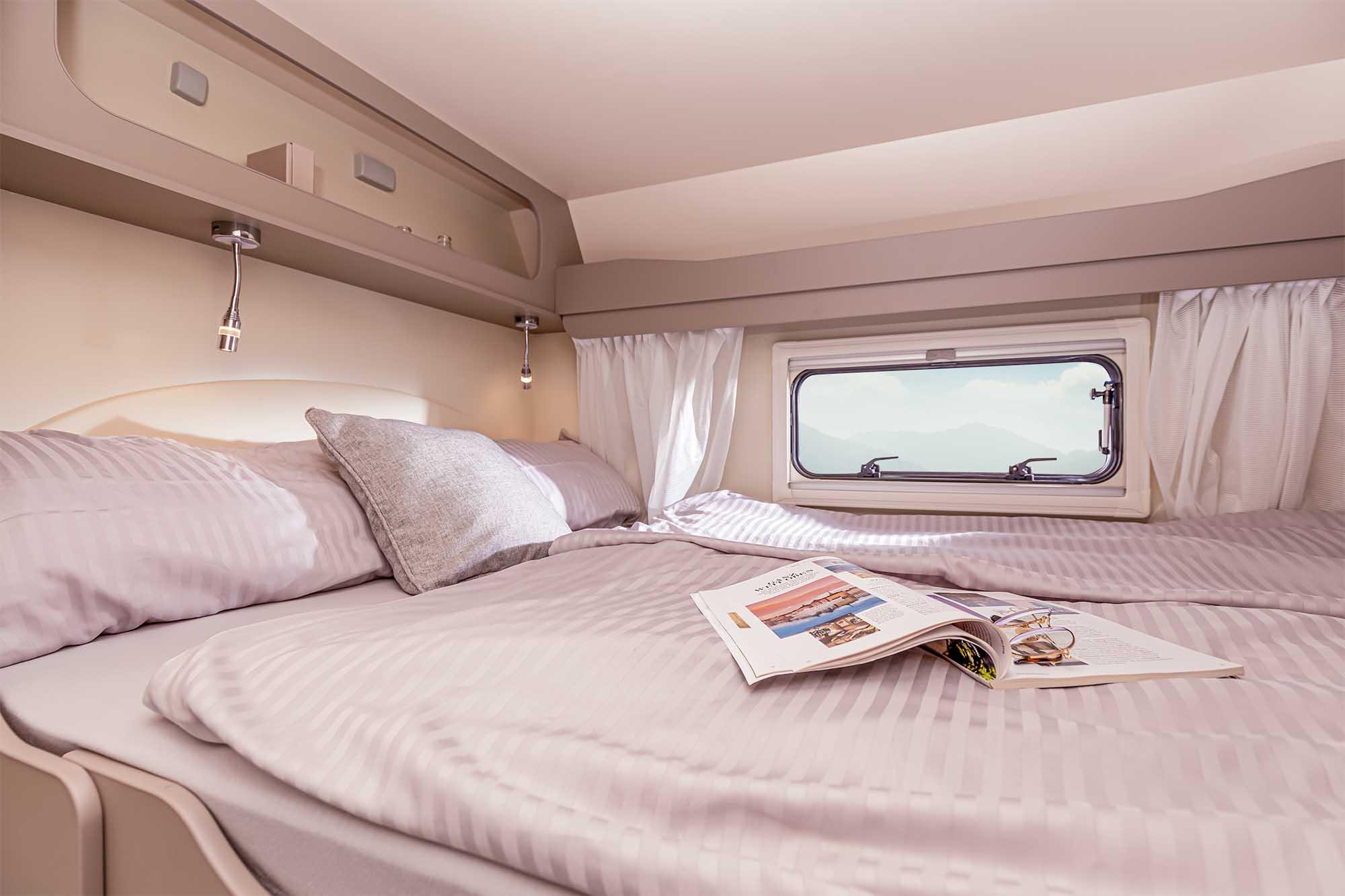 Zwei Personen können im großzügigen Alkoven-Doppelbett schlafen, welches tagsüber im hochgeklappten Zustand ein offenes Raumgefühl ermöglicht.