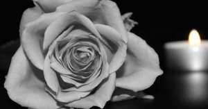 Una rosa nera ed un lumino in segno di lutto.