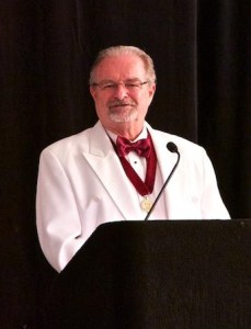 AIBD Fellows are easily identified at formal AIBD functions by their white dinner coats and gold medallions. Here, College Chancellor Jim Lucia is presenting one of many scholarships awarded by the College.