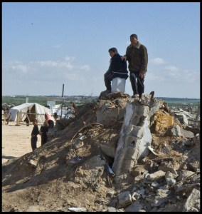 Gaza City, men on rubble of their home, tents in background