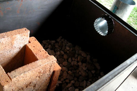 The stove body is filled with pumice, with larger pieces at the bottom and smaller pieces at the top
