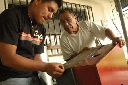 Don Prudencio with Candido Morales working on the Pelton turbine casing.