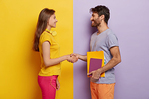 happy-groupmates-meet-after-holidays-shake-hands-agree-work-together-as-team-stand-profile-lovely-woman-with-headphones-meets-friend-unshaven-young-man-holds-notepad-talks-with-female_273609-31089