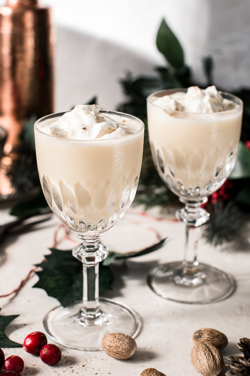 Eggnog cocktail in crystal glasses topped with whipped cream