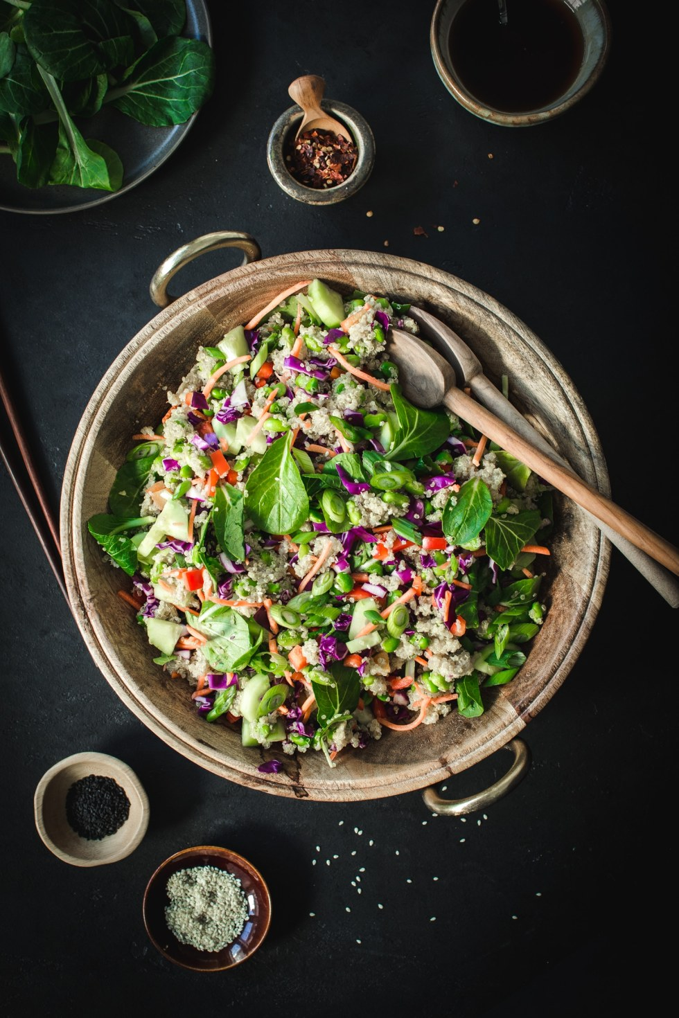 asian sesame quinoa salad in wooden bowl with wooden spoons on black table