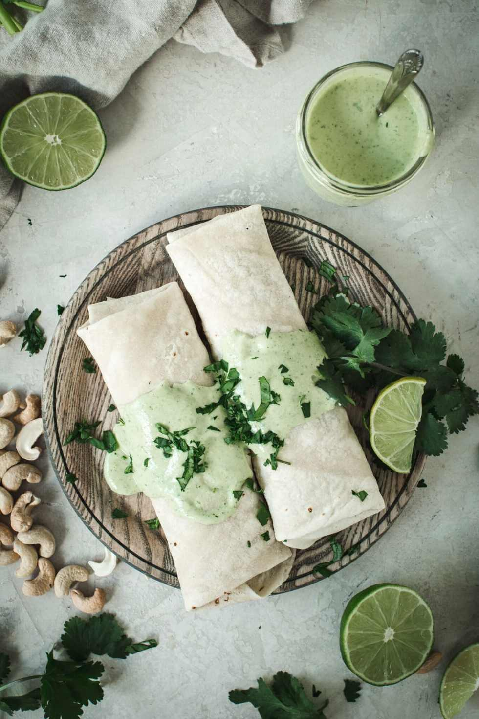 lime crema over burritos on a wooden plate with cilantro