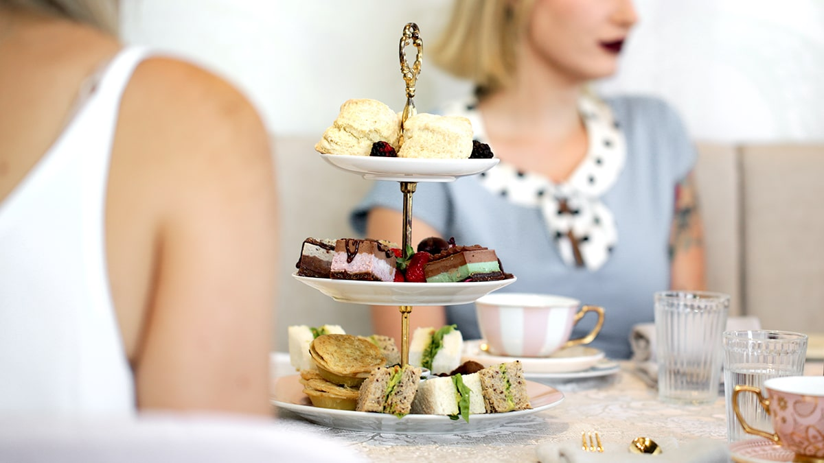 vegan high tea with a lady wearing a blue dress and tea cups