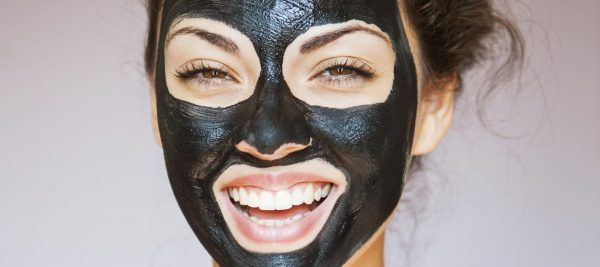 Young beautiful woman with a mask for the face of the therapeutic black mud