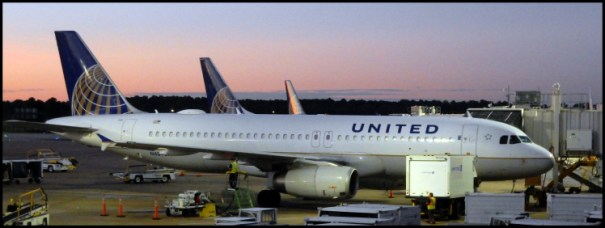 The sun just starting to rise in Houston with the morning United flights getting ready to take on passengers.