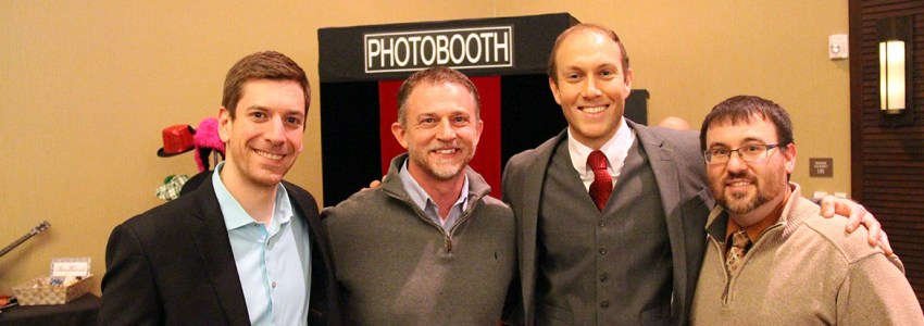 a photot of four men dressed in business casual in front of a photobooth