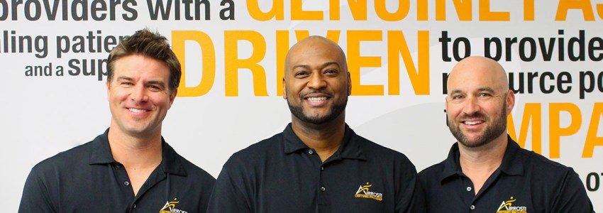 three men photographed with black polos and airrosti logo with words behind them