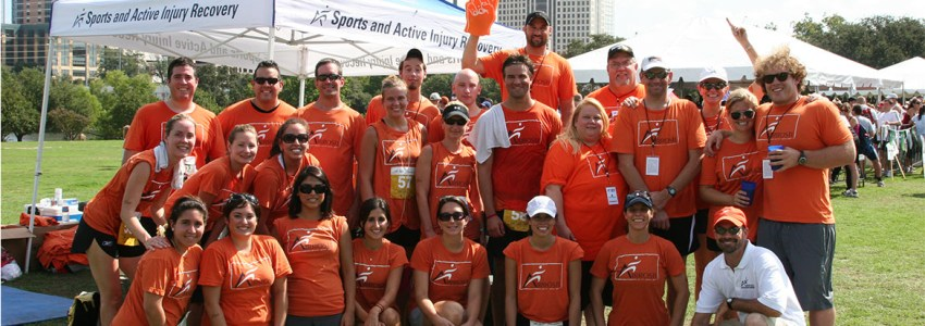 large group of people in orange airrosti t shirts for picture