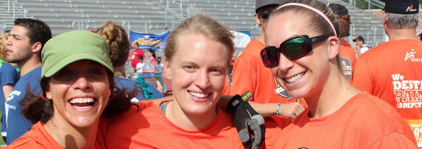 three females smile for photo inside track with orange shirt on
