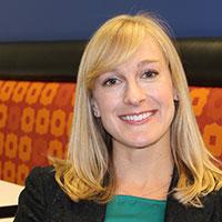 Headshot of Stacy Walker with orange print background