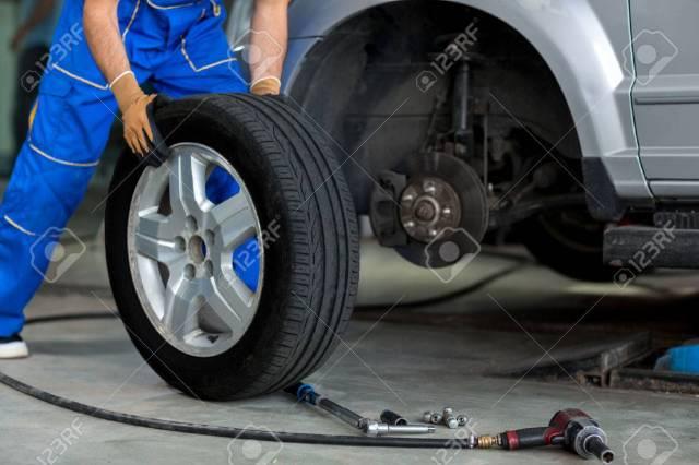 46091361 meccanico cambiare una ruota di una macchina moderna in un workshop  Avvitatori per assemblaggio industriale