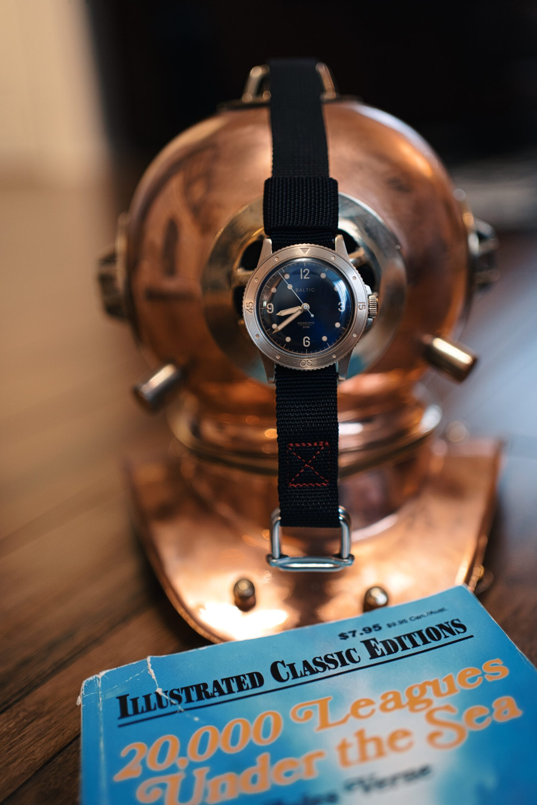 Zulu Alpha black strap on Baltic bronze watch on old diver helmet and cop of 20000 leagues under the sea in foreground