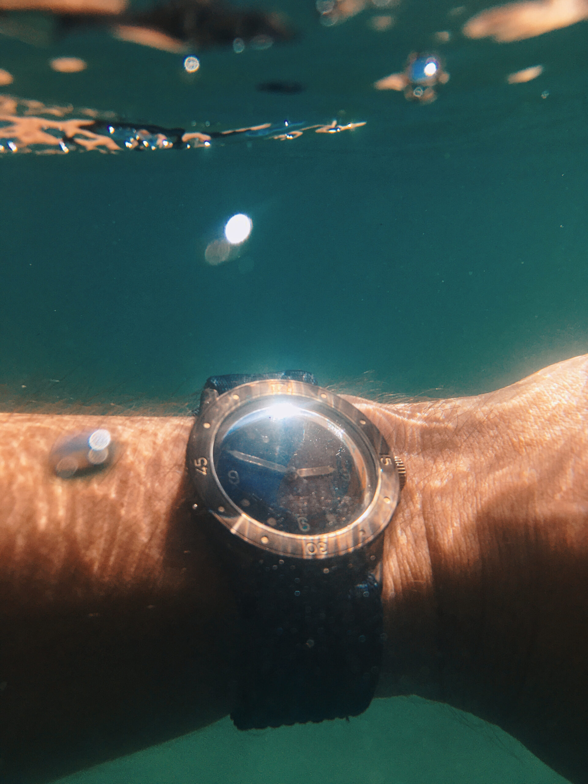 Baltic Aquascaphe Bronze on wrist underwater shot, with two bubbles in foreground and the surface of the water close above