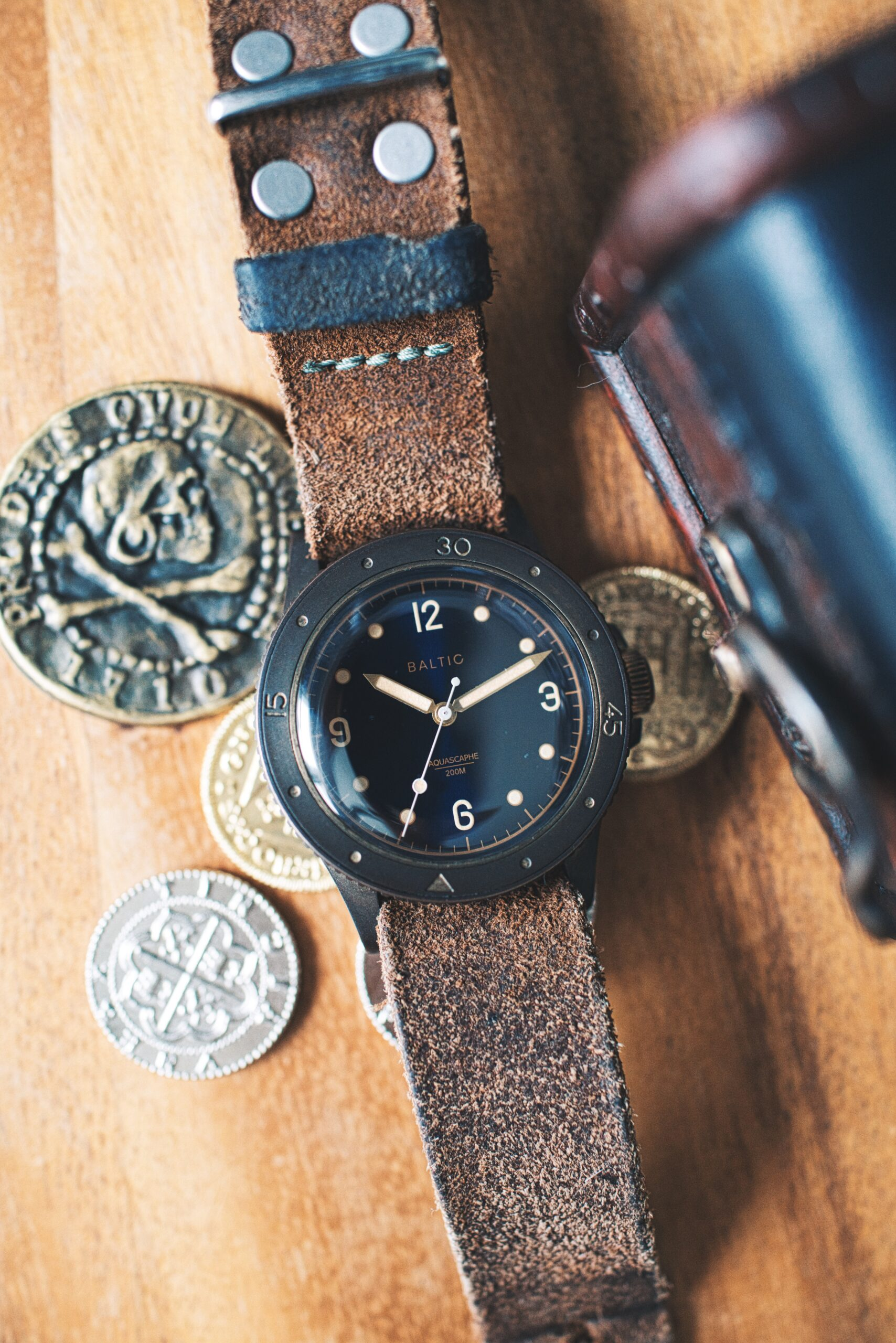 A very patinaed baltic bronze next to old pirate coins, near a small treasure chest sitting atop a wood desktop. Watch on a worn rough leather strap.