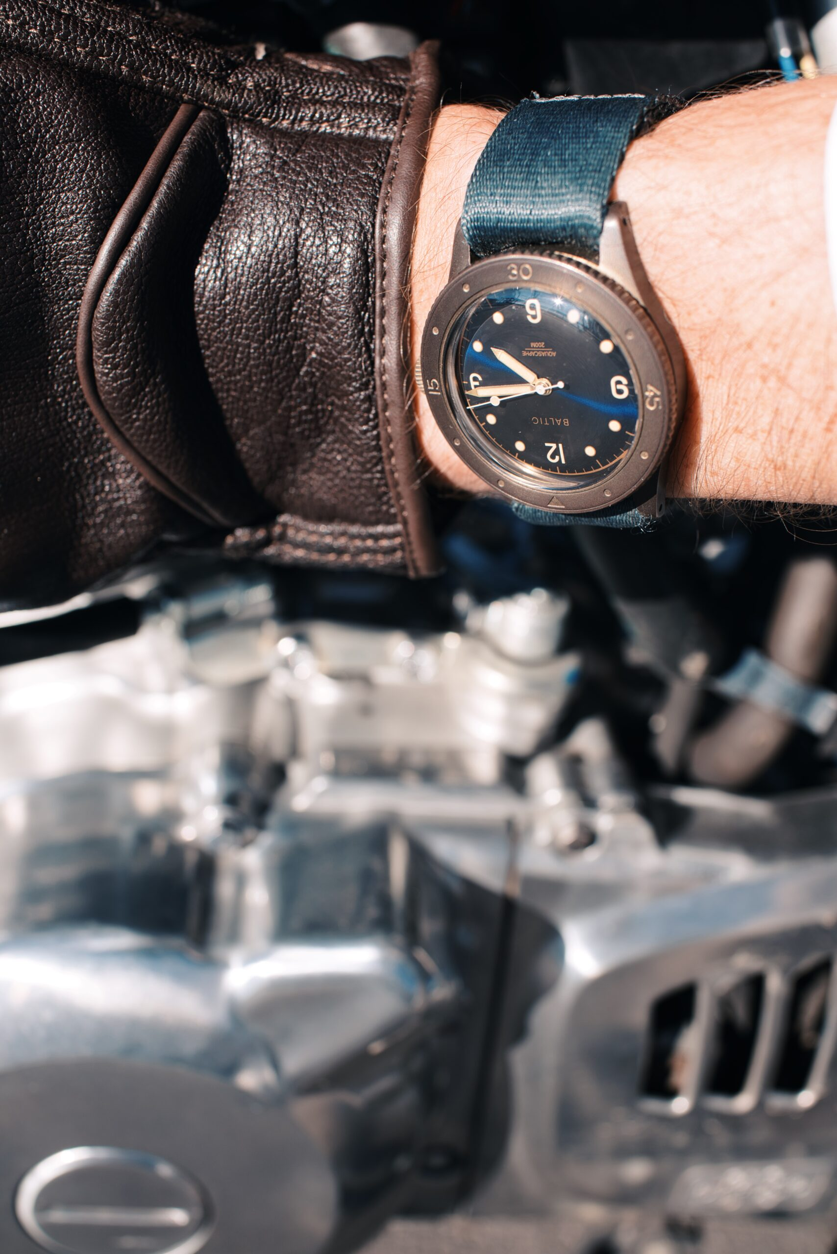Tuning things engine side before riding in the DGR (Distinguished Gentleman's Ride) 2020 with the Baltic bronze on wrist, grey Zulu Alpha strap, and motorcycle engine in background (hand with glove)