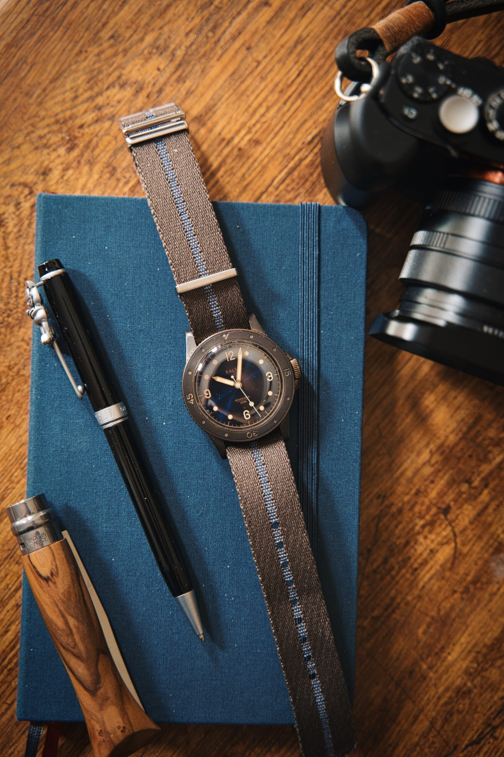 Baltic Bronze on coffee table atop a blue Moleskine, pen next to it, pocket knife and a RX1RmII Camera nearby