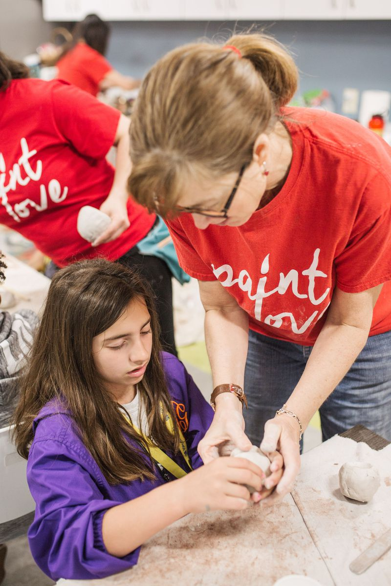 Ellen Gadberry helps a student at Kate's Club create a clay animal mask to talk about how grief expresses itself.