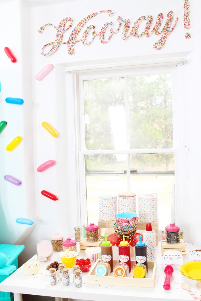 A sprinkle party with sprinkle balloon backdrop, sprinkle covered letters and and ice cream bar!
